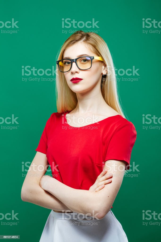 Portrait of Seriuos Girl Wearing Eyeglasses, Red Top and White Skirt on Green Background. Young Beautiful Woman with Sensual Lips and Long Hair in Studio. royalty-free stock photo