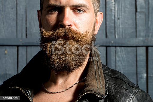 Portrait of sexual brutal unshaven guy with long beard and hendlebar in brown leather jacket looking forward standing on grey wooden background, horizontal picture