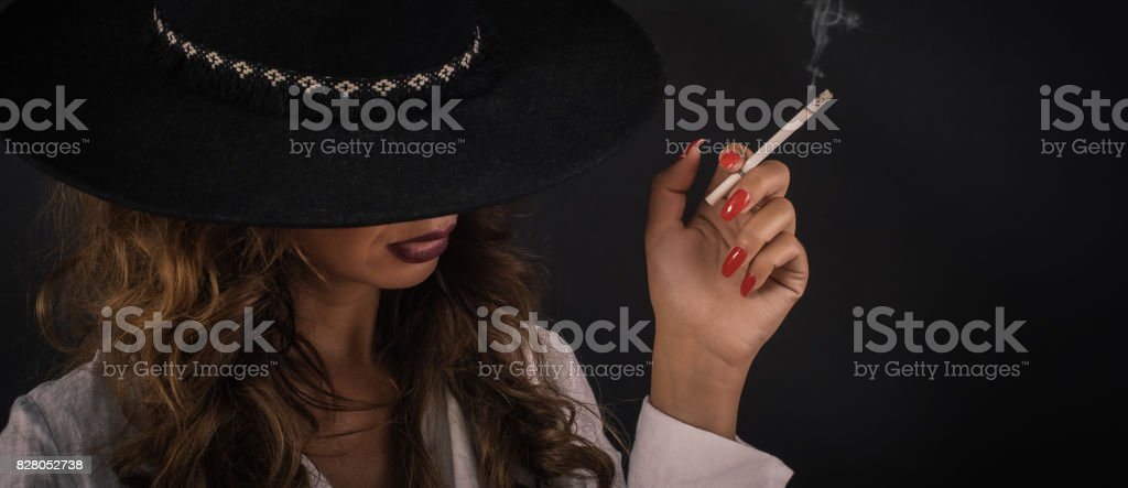 Portrait of sexy elegant lady woman with hat smoking cigarette stock photo