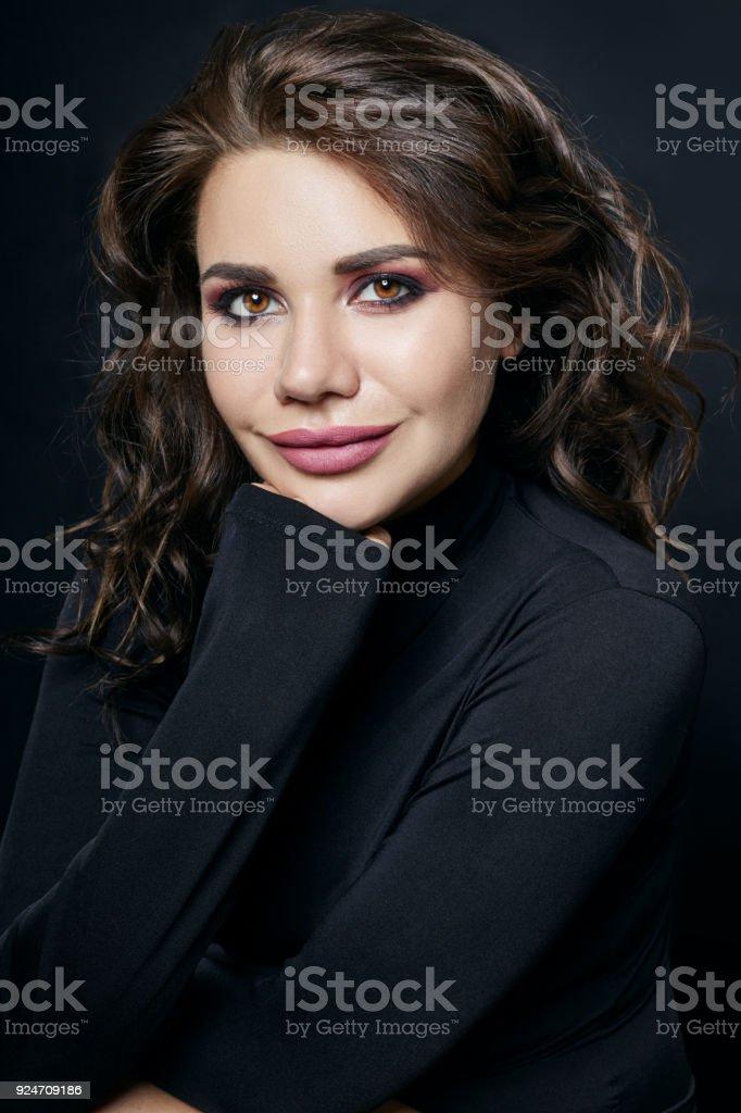 0cf31fece9 Retrato de uma mulher sexy com camisola de gola alta preta com um colar  longo em
