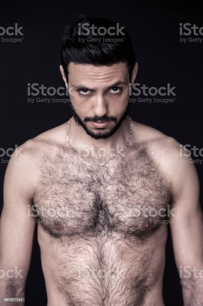 Portrait of shirtless muscular hairy man - Stock image .