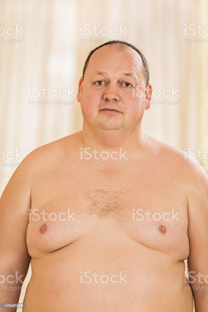 Sad shirtless fat man standing and looking at camera.
