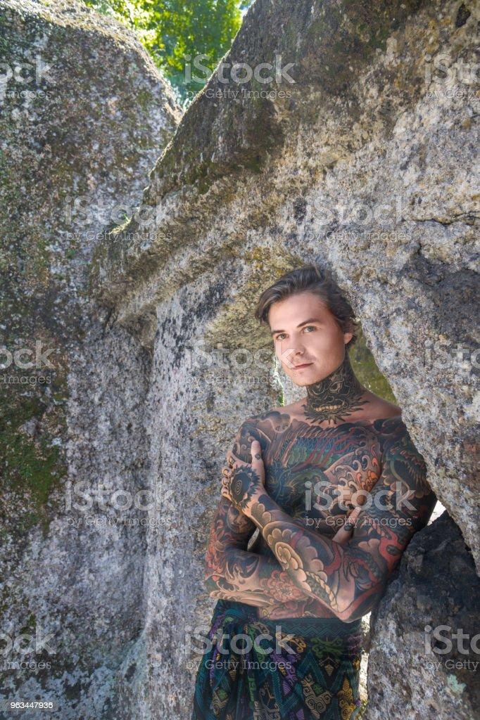 Porträtt av shirtless tatuerade man står vid ruinerna i bali, Indonesien - Royaltyfri Bali Bildbanksbilder