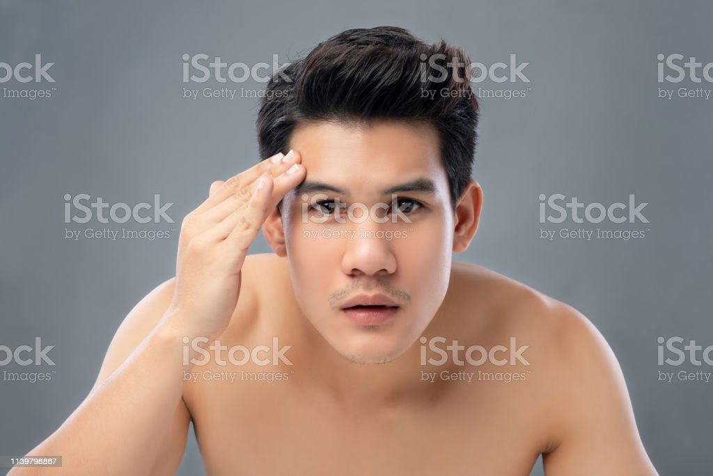 Portrait of shirtless young handsome Asian man checking his face for...