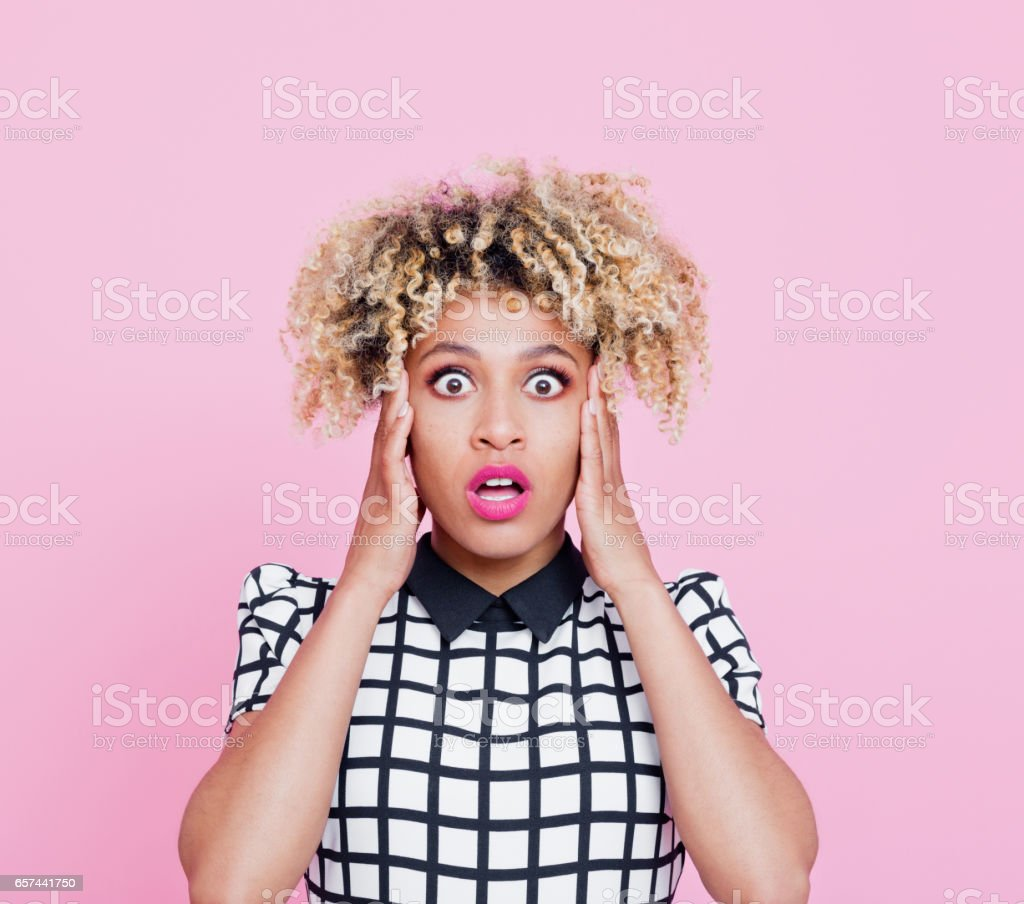 Portrait of shocked afro american young woman Studio portrait of shocked afro american young woman staring at the camera. Pink background. 20-24 Years Stock Photo