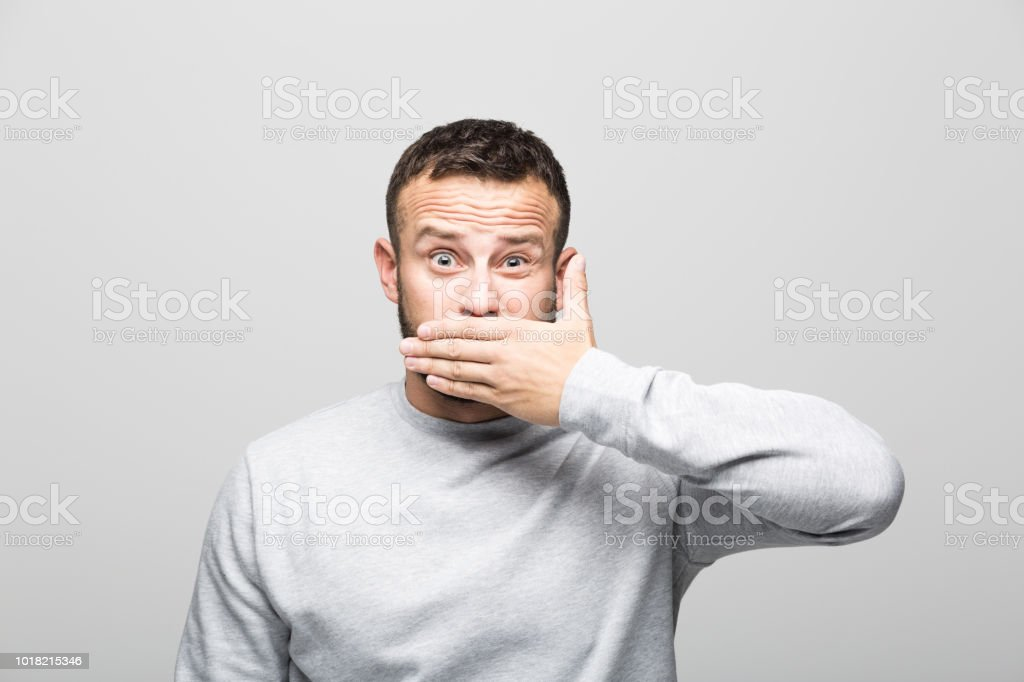 Portrait of shocked bearded young man covering mouth with hand Shocked bearded young man looking away with hand covering mouth. Studio shot, grey background. 30-34 Years Stock Photo
