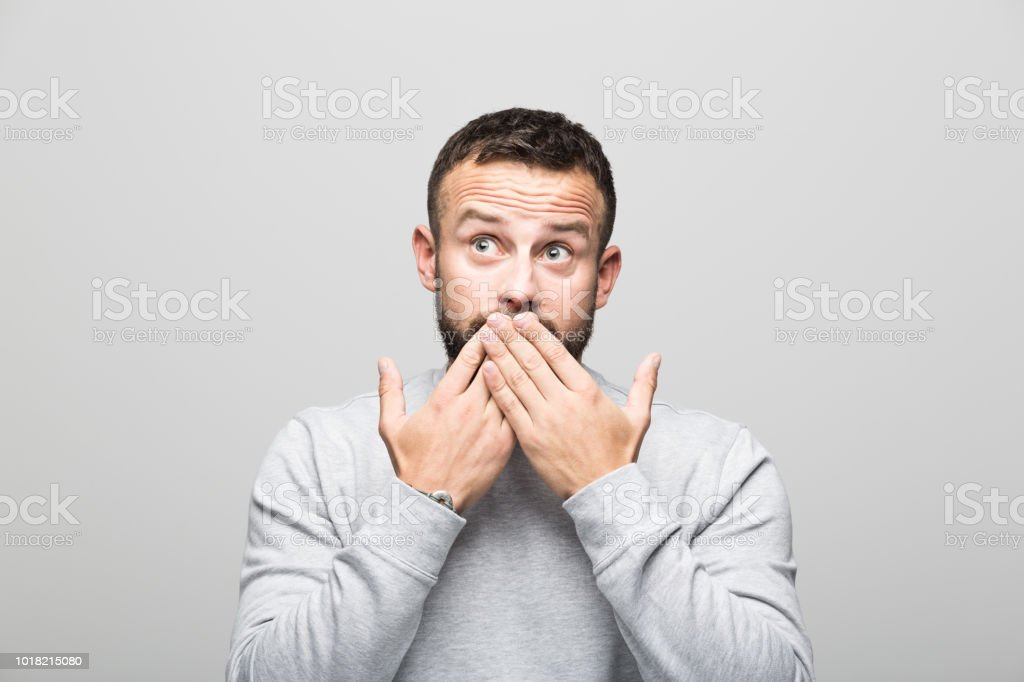 Portrait of shocked bearded young man looking up, grey background Shocked bearded young man looking up with hands covering mouth. Studio shot, grey background. 30-34 Years Stock Photo