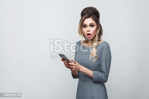 640046924 istock photo Portrait of shocked beautiful blogger teenager wearing in grey dress with pigtail on head standing, using smartphone and watching video with amazed face. 1092612278