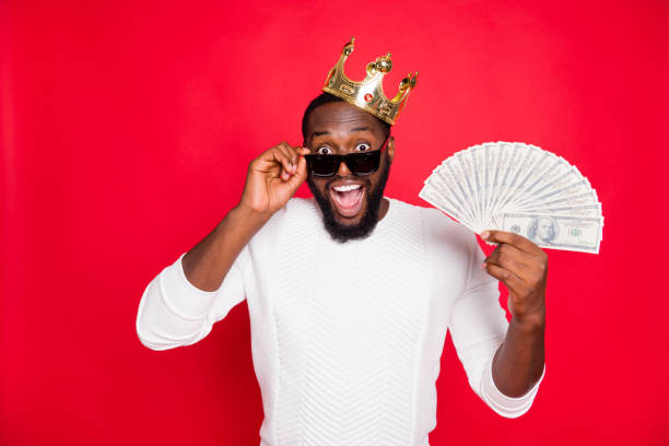 portrait of shocked crazy dark skin man brown hair bearded hold fan of money scream wow win cashback x-mas lottery in million dollars wear gold tiara white jumper isolated over red color background - principe persona nobile foto e immagini stock