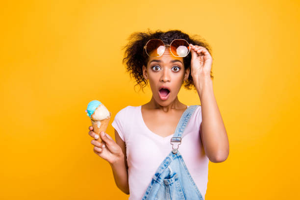 WTF! Portrait of shocked frustrated girl looking out eyeglasses with wide open eyes mouth having ice cream in waffle cone isolated on yellow background WTF! Portrait of shocked frustrated girl looking out eyeglasses with wide open eyes mouth having ice cream in waffle cone isolated on yellow background grimacing stock pictures, royalty-free photos & images