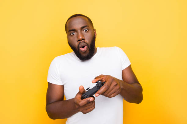 portrait of shocked funny funky crazy mulato man, playing online game, opened mouth, plump lips, isolated over bright vivid yellow background - man joystick imagens e fotografias de stock