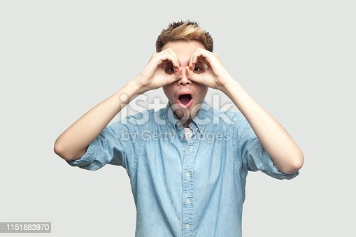 Portrait of shocked handsome young man in light blue shirt standing with hands on eyes binoculars gesture and looking at camera with surprised face. indoor studio shot on grey background copy space.