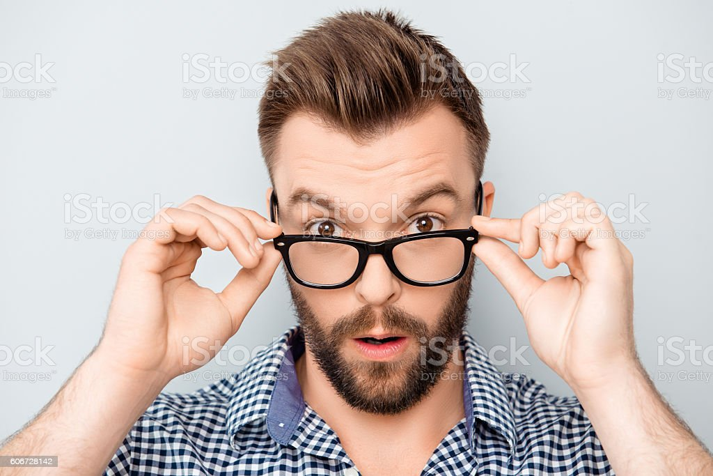Portrait of shocked modern man touching his spectacles stock photo