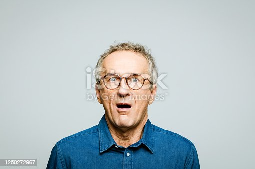 Portrait of elderly man wearing white denim shirt and glasses staring at camera with mouth open. Terrified senior entrepreneur, studio shot against grey background.