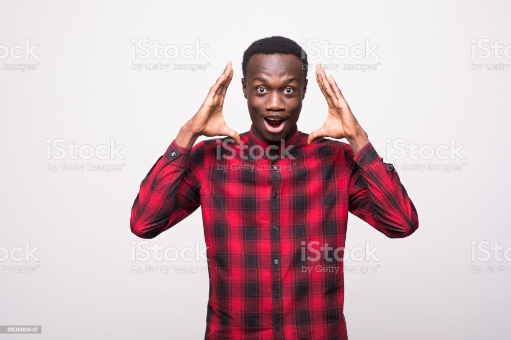 Portrait of shocked young African American man looking at the camera in surprise, stunned with some incredible story, holding hands on head. Human expressions and emotions stock photo