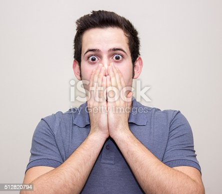 istock Portrait of shocked young man against colored background 512820794