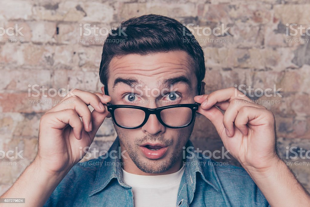 Portrait of shocked young man in glasses with open mouth stock photo