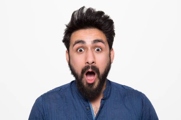 Portrait of shocked young man over white background Portrait of shocked young man over white background raised eyebrows stock pictures, royalty-free photos & images
