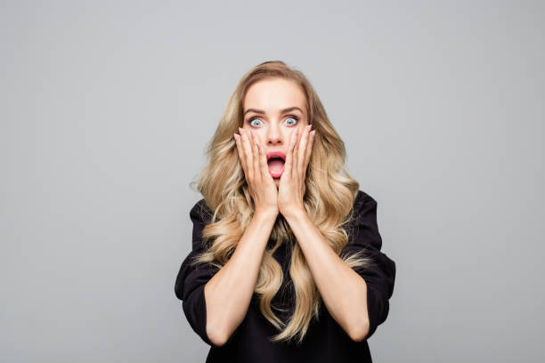 Portrait of shocked young woman with hands on face stock photo