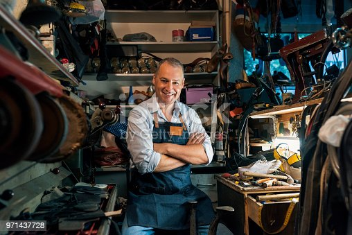 Photo of happy Caucasian mature, gray hair craftsman wearing denim apron making luxury handmade man or woman shoes in his small workshop while sitting with arms crossed. Professional diligent handsome shoemaker heeling footwear on machine at the shop, looking at the camera.