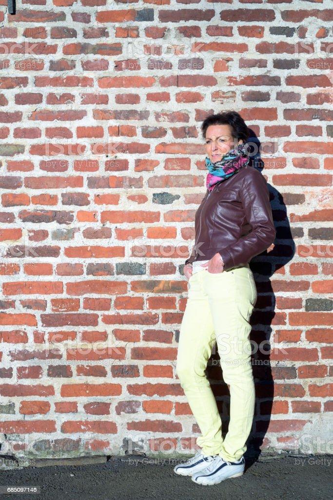 Retrato de mujer madura pelo corto de pie contra la exterior del muro de ladrillo foto de stock libre de derechos