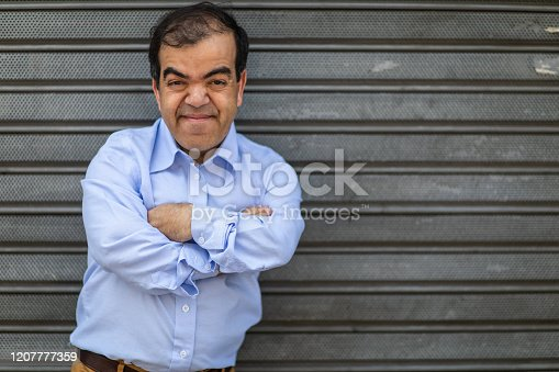 Portrait of well dressed short man standing in front of rolling garage door with arms crossed and looking at camera