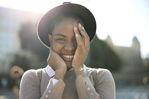Partial front view of mid 30s woman standing outdoors on sunny day in hat and casual clothing cradling her face as she smiles at camera with great happiness.