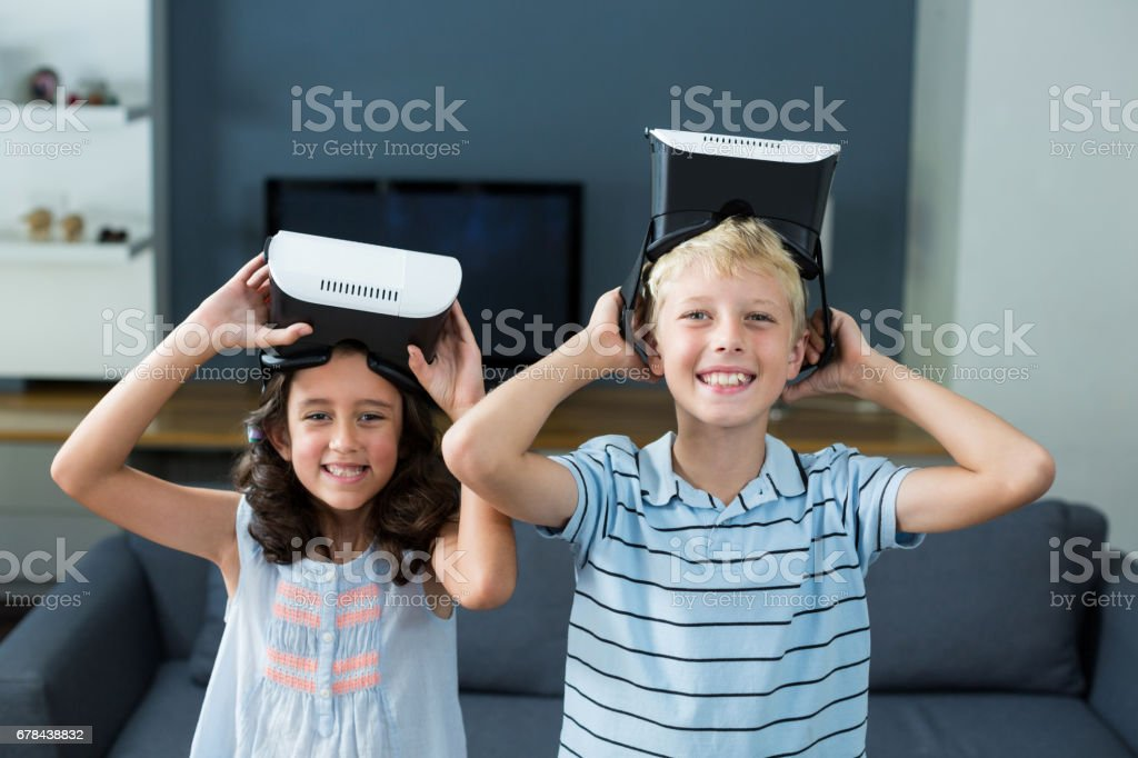 Portrait of siblings holding virtual reality headset in living room royalty-free stock photo