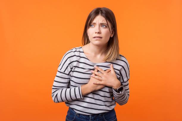 porträt von kranken verärgerten frau mit braunen haaren in langärmeligen gestreiften hemd. indoor-studio-aufnahme isoliert auf orangefarbenem hintergrund - herz lungen training stock-fotos und bilder