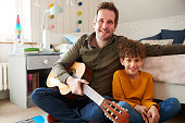 istock Portrait Of Single Father At Home With Son Playing Acoustic Guitar In Bedroom 1154944342