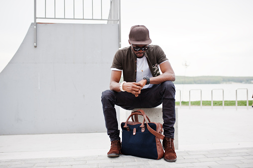627398448 istock photo Portrait of sitting stylish african american man wear on sunglasses and cap, looking on his watches outdoor. Street fashion black man. 675760404