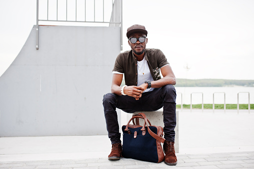 627398448 istock photo Portrait of sitting stylish african american man wear on sunglasses and cap, looking on his watches outdoor. Street fashion black man. 675760450