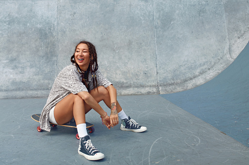 Portrait Of Skater Girl In Skatepark. Female Teenager In Casual Outfit Sitting On Skateboard Against Concrete Wall. Summer Skateboarding With Modern Sport Equipment As Part Of Active Lifestyle.