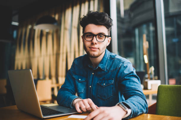 Portrait of skilled male it developer working remotely in cafe interior using wireless connection and laptop computer,young man in spectacles for vision protection while learning via netbook stock photo