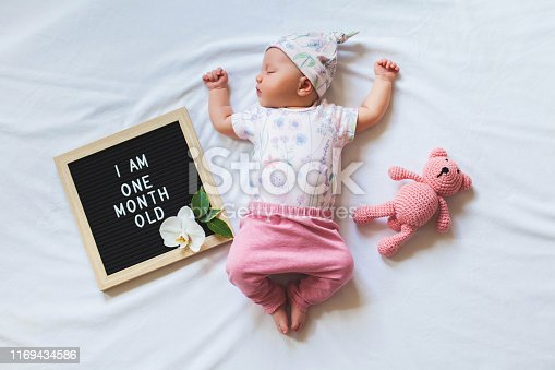 508167718 istock photo Portrait of sleeping one month old newborn baby girl laying between letter board and teddy bear. Flat lay composition. 1169434586
