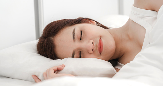 Portrait of sleeping young asia woman enjoy and relax lying on the bed with close eyes in bedroom at home.asian beauty