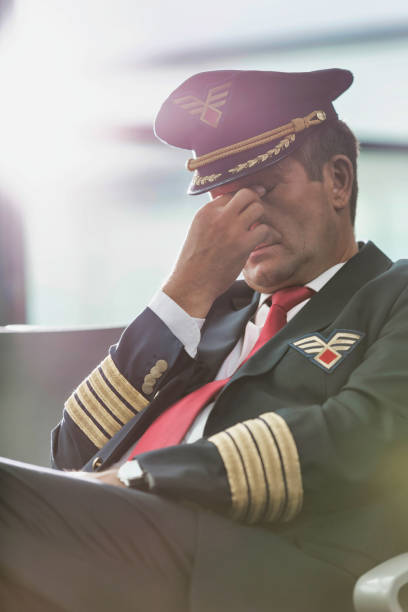 Portrait of sleepy and overworked pilot sitting in airport stock photo