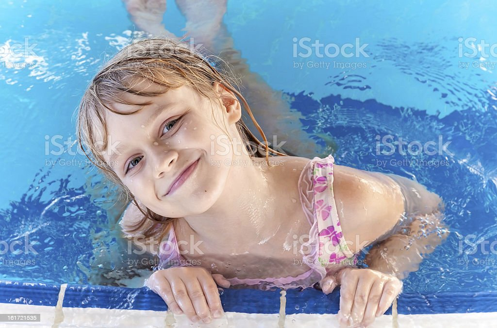 Portrait of slightly smiling little blond girl in a pool royalty-free stock photo