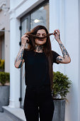 Beautiful slim girl with tattoos  wearing casual  black clothes playing with her hair outside. Hiding face behind long hair. Alternative lifestyle. Portrait of tattooed young female model in black.