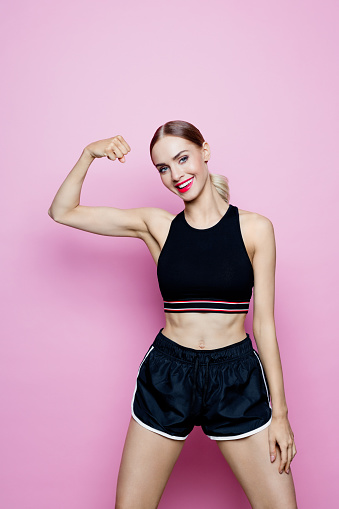 657442382 istock photo Portrait of slim woman in sports clothing against pink background 1224570147