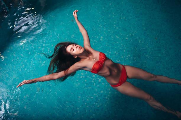 Porträt einer schlanken jungen Frau entspannen im Schwimmbad schwimmend auf dem Rücken – Foto