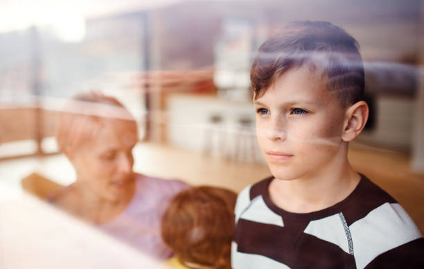 a portrait of small boy with family at home, looking out of window. - boy looking out window stock pictures, royalty-free photos & images