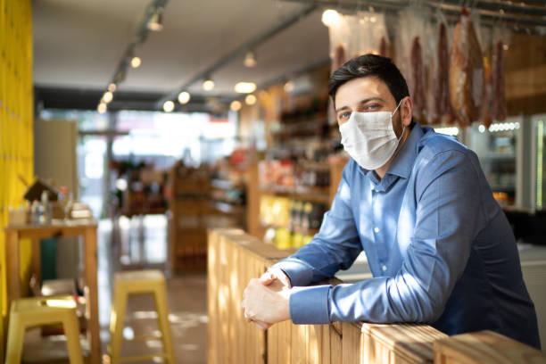 ritratto di piccolo imprenditore proprietario con maschera facciale - bancarella foto e immagini stock