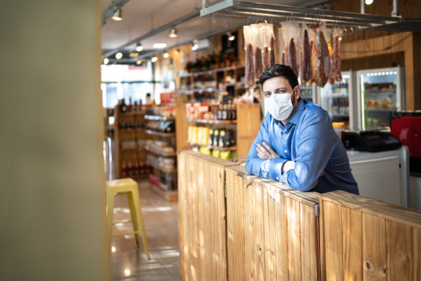 Portrait of small business man owner with face mask stock photo