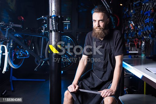952953976istockphoto Portrait of small business owner of young man with beard. Guy bicycle mechanic workshop worker sitting with tool in his hand in a working black clothes in an apron in the background of a bicycle shop 1133364085