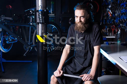 952953976istockphoto Portrait of small business owner of young man with beard. Guy bicycle mechanic workshop worker sitting with tool in his hand in a working black clothes in an apron in the background of a bicycle shop 1133364094