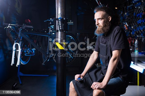 952953976istockphoto Portrait of small business owner of young man with beard. Guy bicycle mechanic workshop worker sitting with tool in his hand in a working black clothes in an apron in the background of a bicycle shop 1133364096