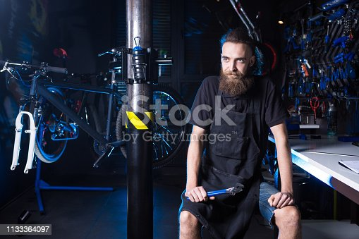 952953976istockphoto Portrait of small business owner of young man with beard. Guy bicycle mechanic workshop worker sitting with tool in his hand in a working black clothes in an apron in the background of a bicycle shop 1133364097