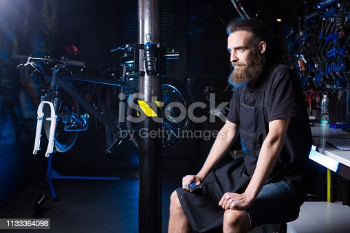 952953976istockphoto Portrait of small business owner of young man with beard. Guy bicycle mechanic workshop worker sitting with tool in his hand in a working black clothes in an apron in the background of a bicycle shop 1133364098