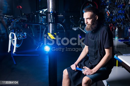 952953976istockphoto Portrait of small business owner of young man with beard. Guy bicycle mechanic workshop worker sitting with tool in his hand in a working black clothes in an apron in the background of a bicycle shop 1133364104